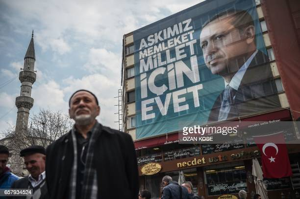 TOPSHOT A man stays next to giant poster of Turkish President Recep Tayyip Erdogan during a rally in support of the Turkish President on March 26...