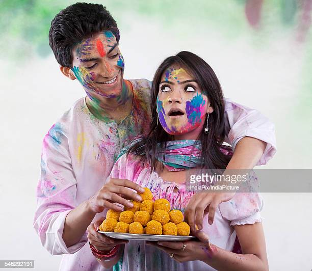 Man stealing a laddoo from a tray