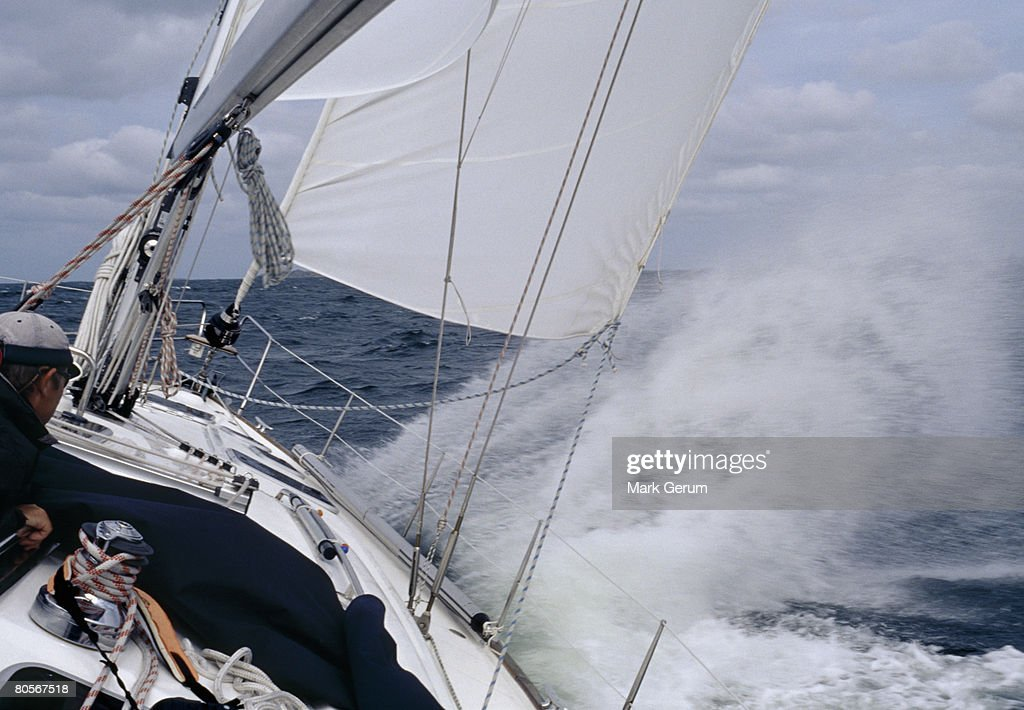 A man steering a yacht in rough weather