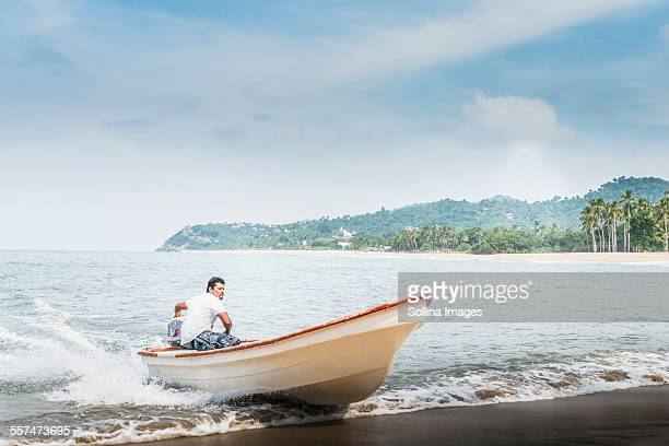 Man steering boat onto beach