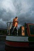 Man steering houseboat in storm