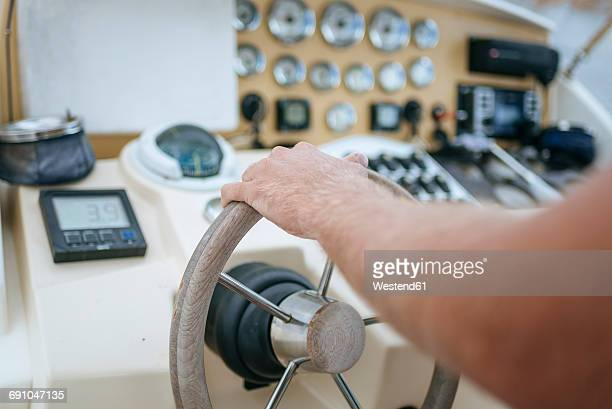 Man steering motor boat, close up