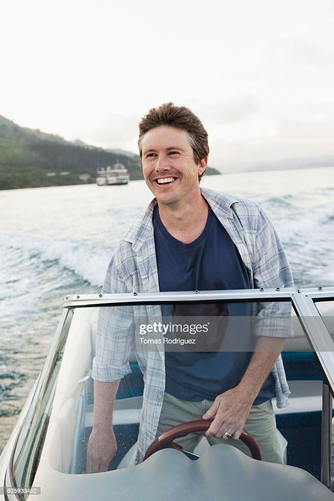 Man steering motorboat : Stock Photo