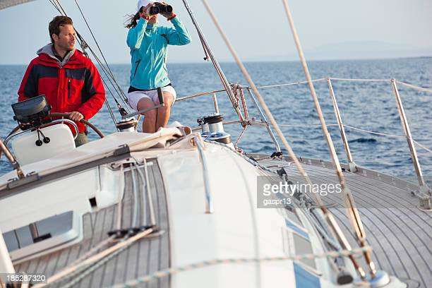 Man steering sailboat out at sea with female passenger