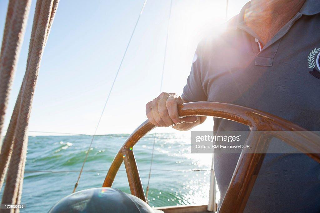 Man steering yacht