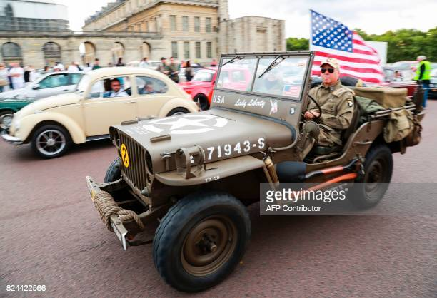 A man steers a WWII US military jeep past the Chateau de Vincennes on July 30 2017 at the start of the '10th Vincennes en Anciennes' vintage vehicles...