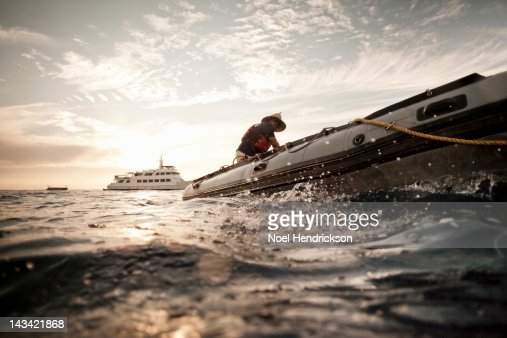 A man steers an inflatable boat for scuba divers : Stock Photo
