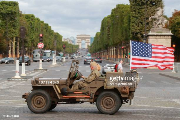 A man steers his WWII US military jeep on July 30 2017 during the '10th Vincennes en Anciennes' vintage vehicles parade on Place de la Concorde in...
