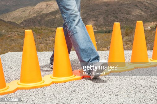 Man stepping in-between a row of safety cones