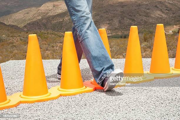 Homem Pisar entre uma linha de cones de segurança