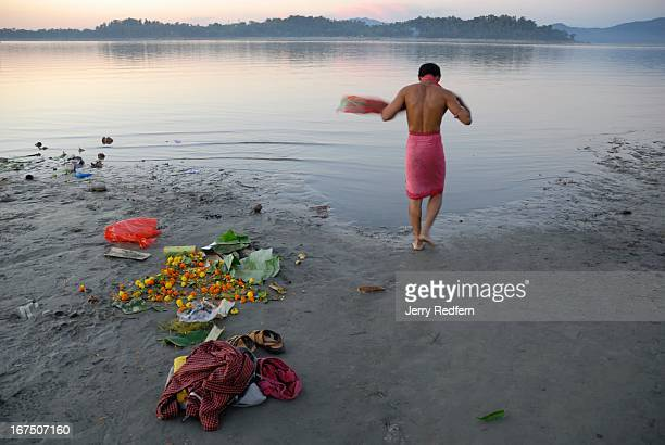 A man steps into the Brahmaputra River a holy place for Hindus for a bath before praying before the rising full moon at Guwahati India Hindus view...