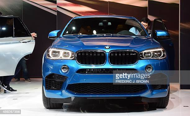 A man steps into the driver's seat of BMW's justunveiled X6M on display at the LA Auto Show's press and trade day in Los Angeles California on...