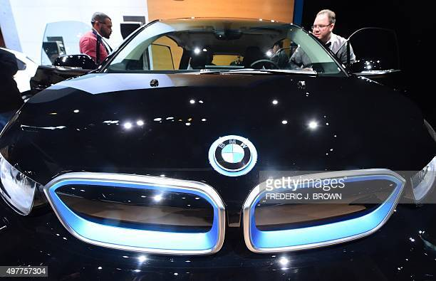 A man steps into the driver's seat of the allelectric BMW i3 at the 2015 Los Angeles Auto Show in Los Angeles California on November 18 2015 The LA...