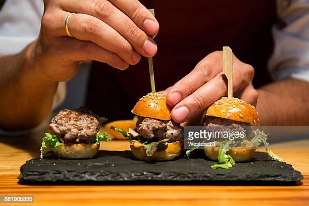 Man sticking a skewer in a mini burger of red tuna