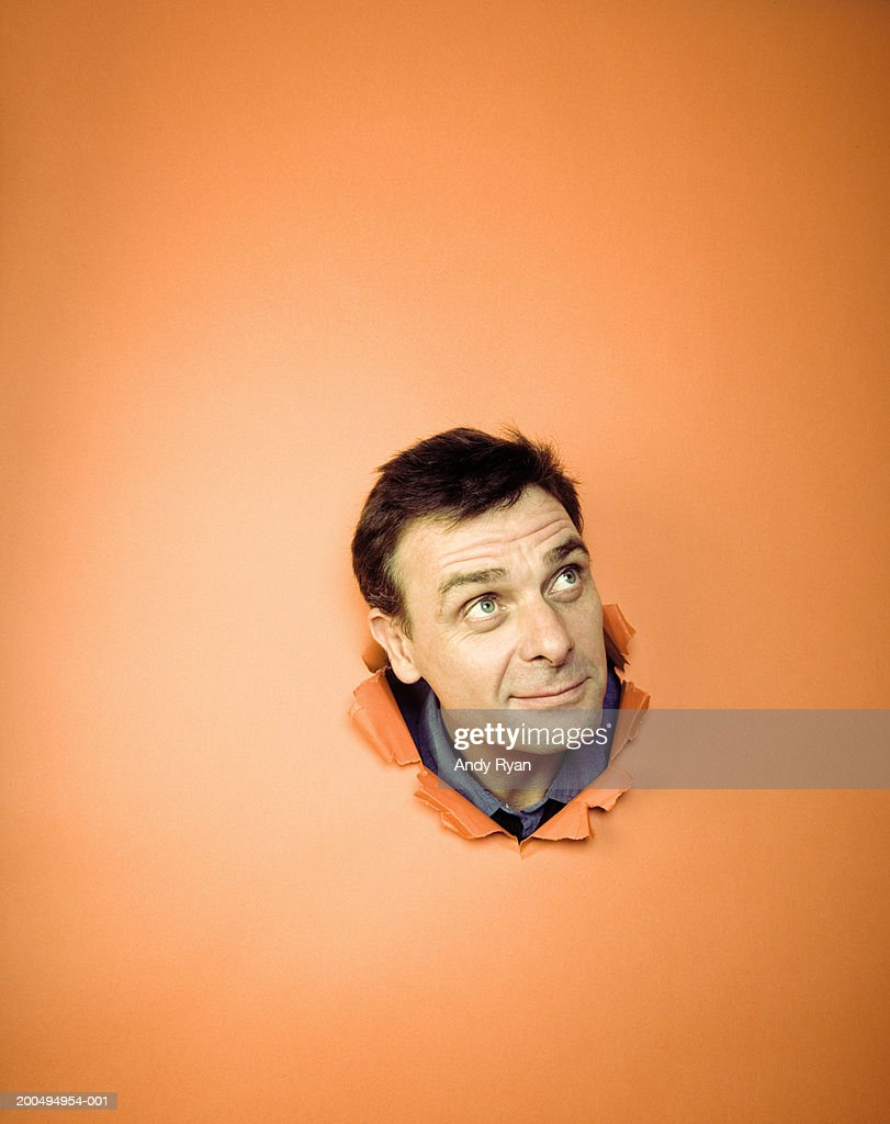 Man sticking head through hole in orange wall, looking up, smiling : Stock Photo