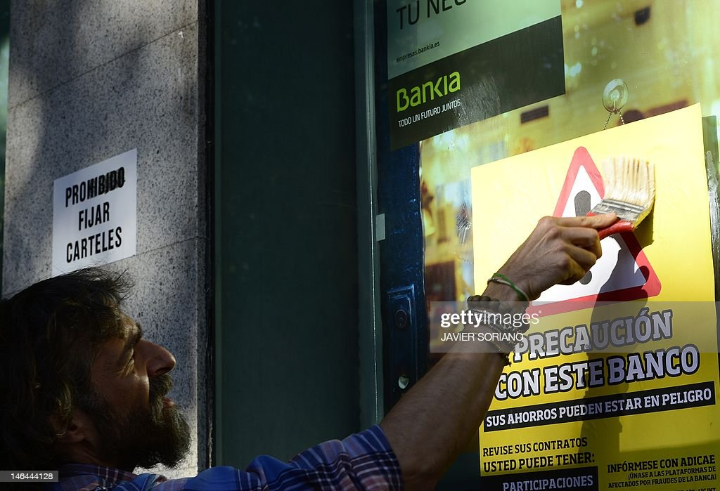 A man sticks a placard reading 'Caution with this bank' on the windowcase of a Spanish bank Bankia office during a demonstration against bank fraud on June 16, 2012 in Madrid. Spain's 'indignant' activists filed a criminal complaint on June 14, 2012 against the former management of Bankia, whose partial nationalisation helped push Madrid to seek a massive EU bailout. Last month, Bankia revised its 2011 results from a net profit of 309 million euros ($387 million) to a loss of nearly three billion euros and asked the state for a bailout of 19 billion euros, the largest in Spanish history.