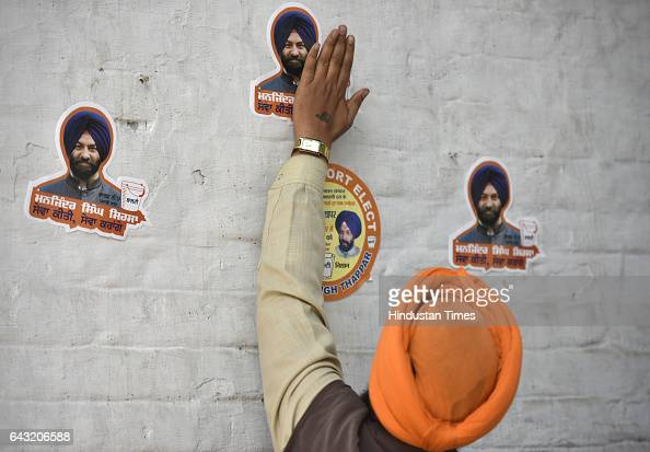 A man sticks a poster into a Shiromani Akali Dal Badal party office wall during the Delhi Sikh Gurdwara Management Committee DSGMC for upcoming...
