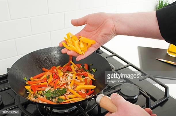 男性フライパンで焼かれる野菜炒め物