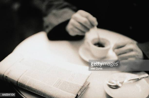 Man Stirring His Coffee at a Cafe
