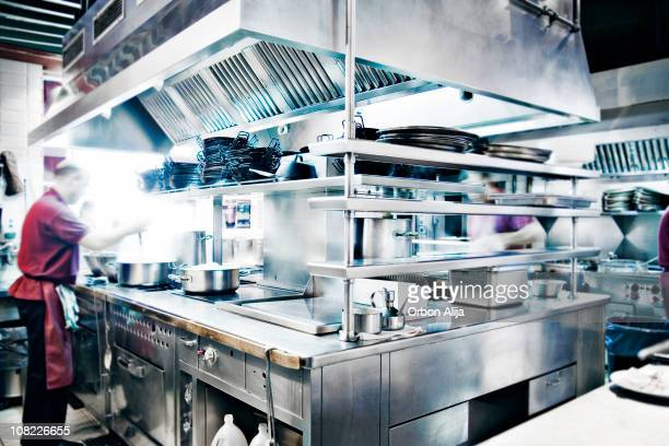 Man Stirring Pot in Stainless Steel Restaurant Kitchen