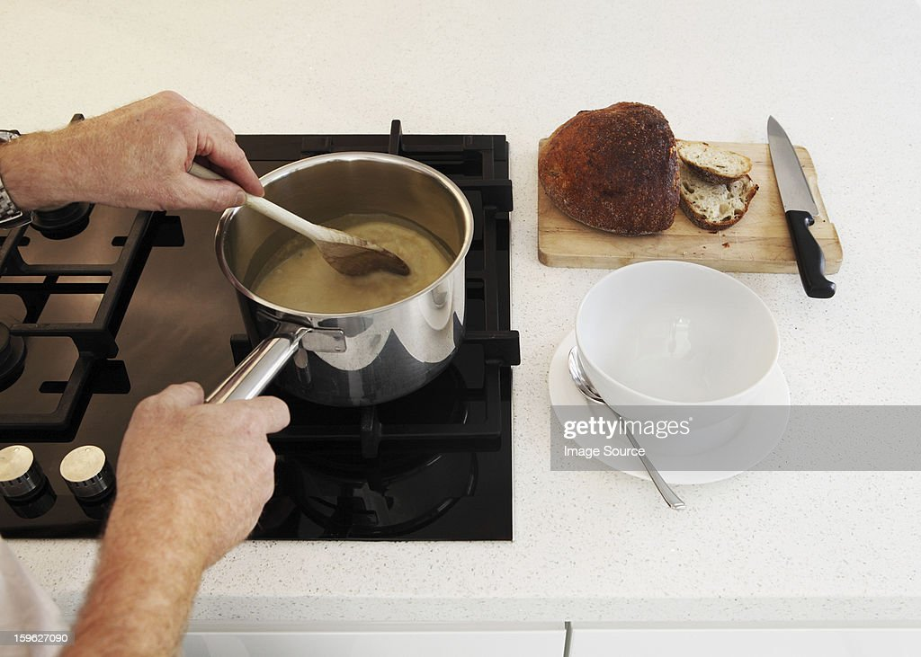 Man stirring saucepan of soup on hob