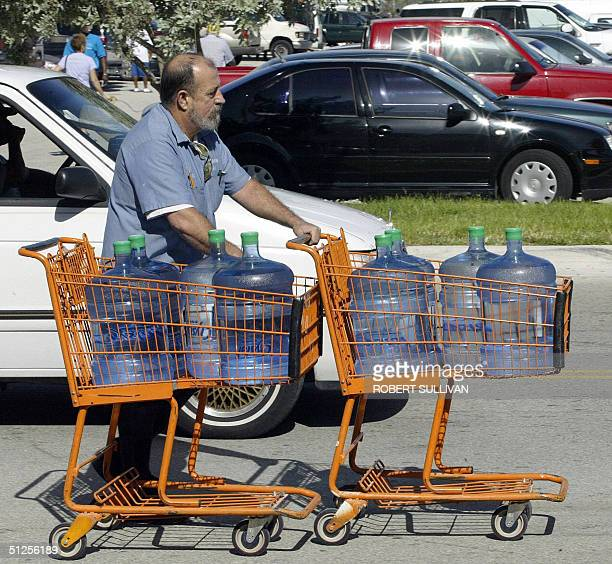 A man stocks up on drinking water to prepare for Hurricane Frances in Ft Lauderdale Florida 02 September 2004 Frances lashed the Bahamas today as it...