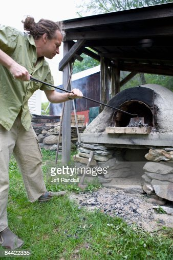 Man stoking outdoor stove : Stock Photo