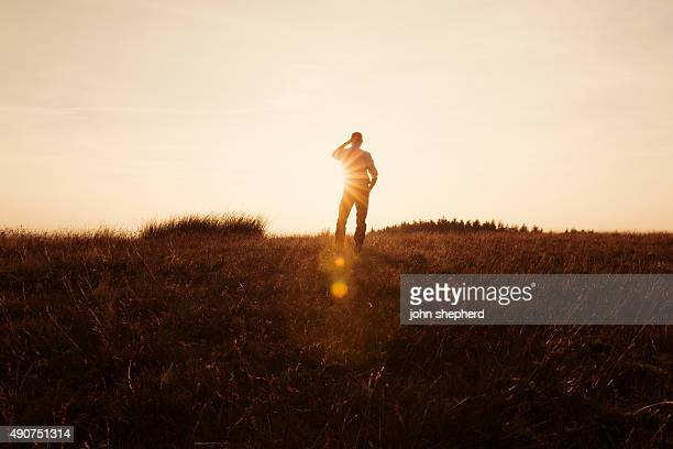 Man Stood in the countryside looking at the sunset
