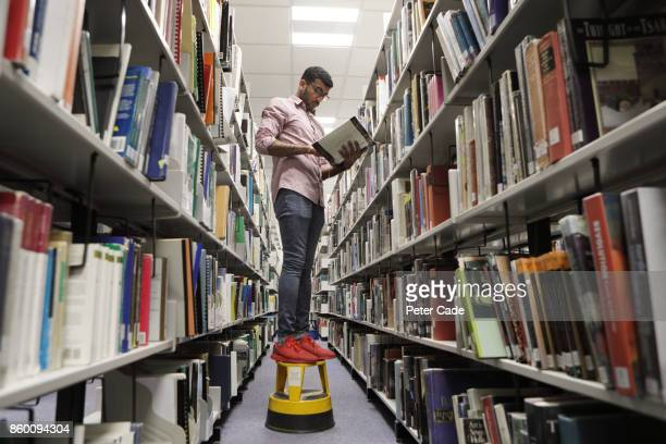 Man stood on stool in library reading book from shelf