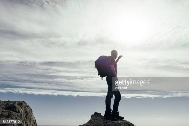 man stood on top of rocks backlit in sunflare with backpack.