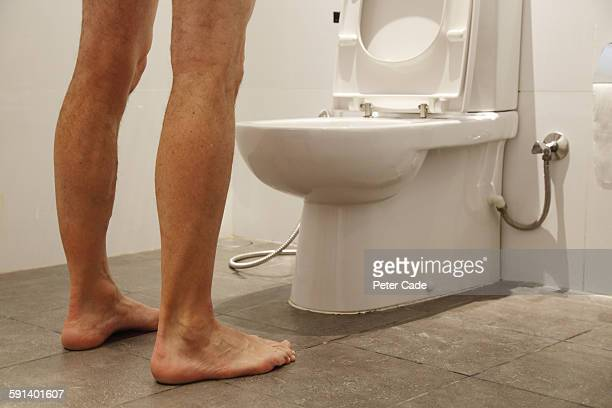 Man stood over toilet