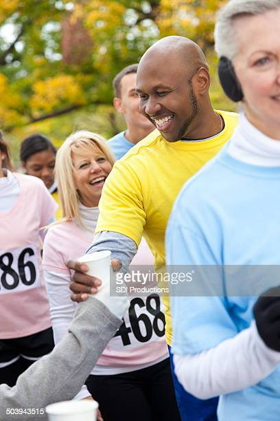 Man stopping for water during charity walk or race