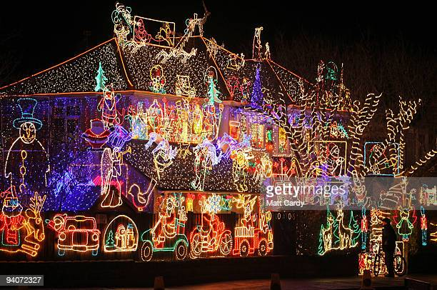 A man stops to admire Christmas festive lights displayed on a detached house in a suburbian street in Melksham December 5 2009 in Melksham England...