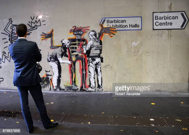 A man stops to admire street art created in September 2017 near the Barbican Centre in London England by Banksy an anonymous Englandbased graffiti...