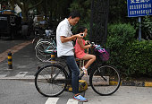A man stops to check his mobile phone while his daughter waits on a street in Beijing on July 22 2016 / AFP / GREG BAKER