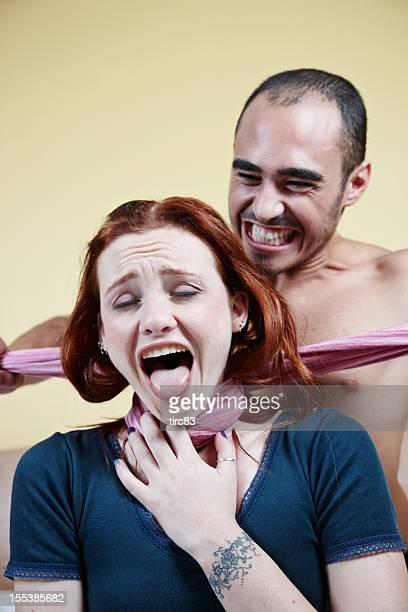 Man strangling woman with scarf on bed