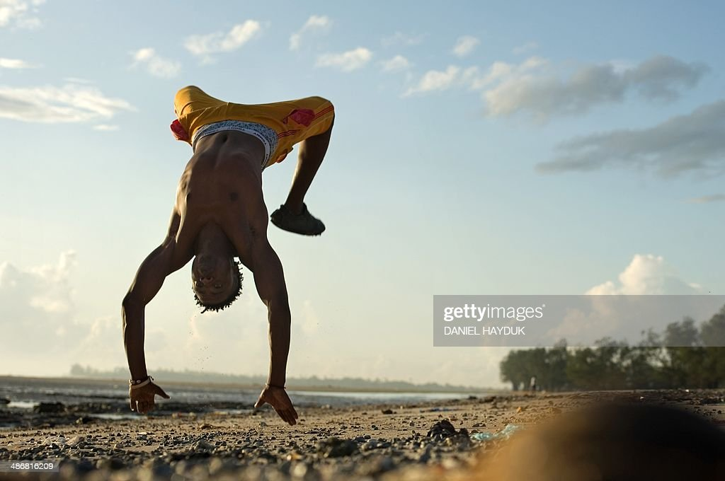 A man streches on a beach in Dar es Salaam on April 26, 2014, as Tanzania celebrates today the 50th anniversary of the Union Day, which celebrates the union of Zanzibar and Tanganyika. AFP PHOTO Daniel Hayduk