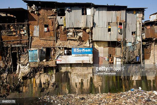 A man stretches as he looks out of his dwelling in the Dharavi slum on February 3 2009 in Mumbai India The redevelopment of asia's largest slum the...