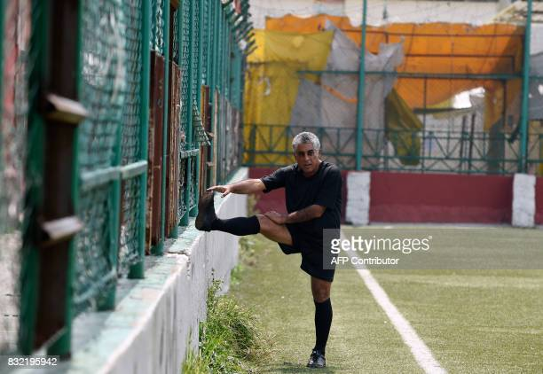 A man stretches before a match in which both teams have black uniforms as part of a performance called 'Todos Contra Todos' of Chilean artist Camilo...