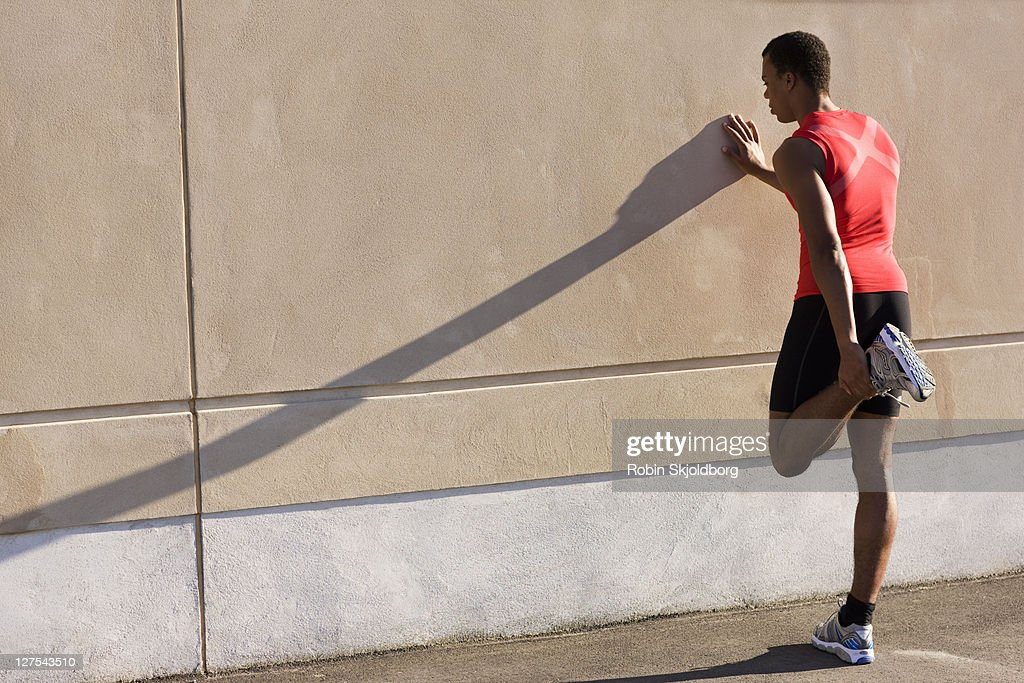 Man stretching against wall