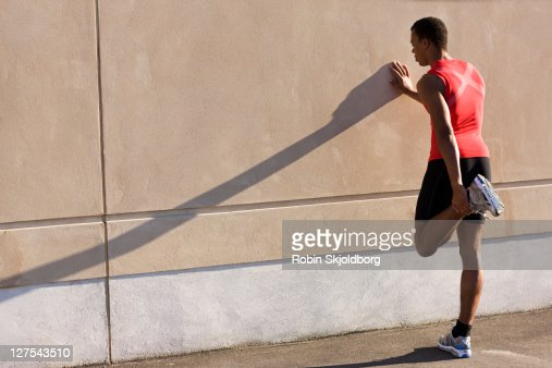Man stretching against wall : Stock Photo