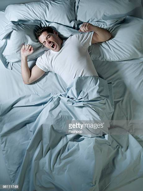 Man stretching and yawning in bed