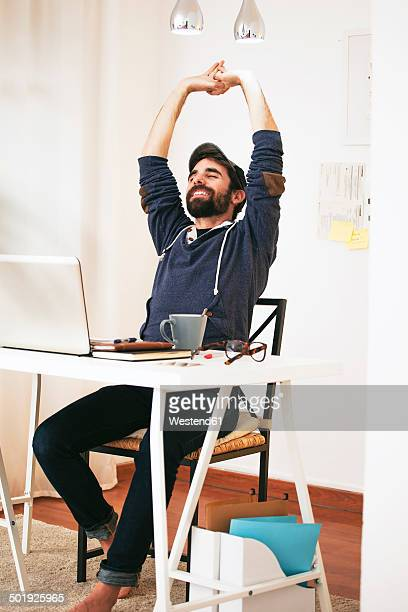 Man stretching at modern home office