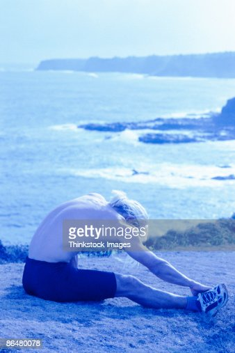 Man stretching by coast : Stock Photo