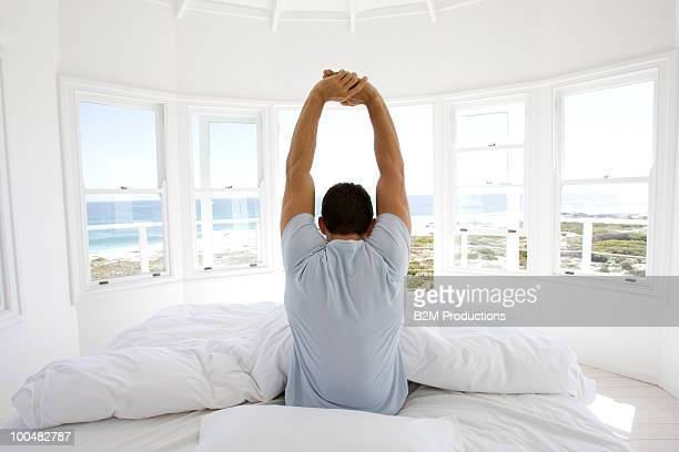 Man stretching in bed