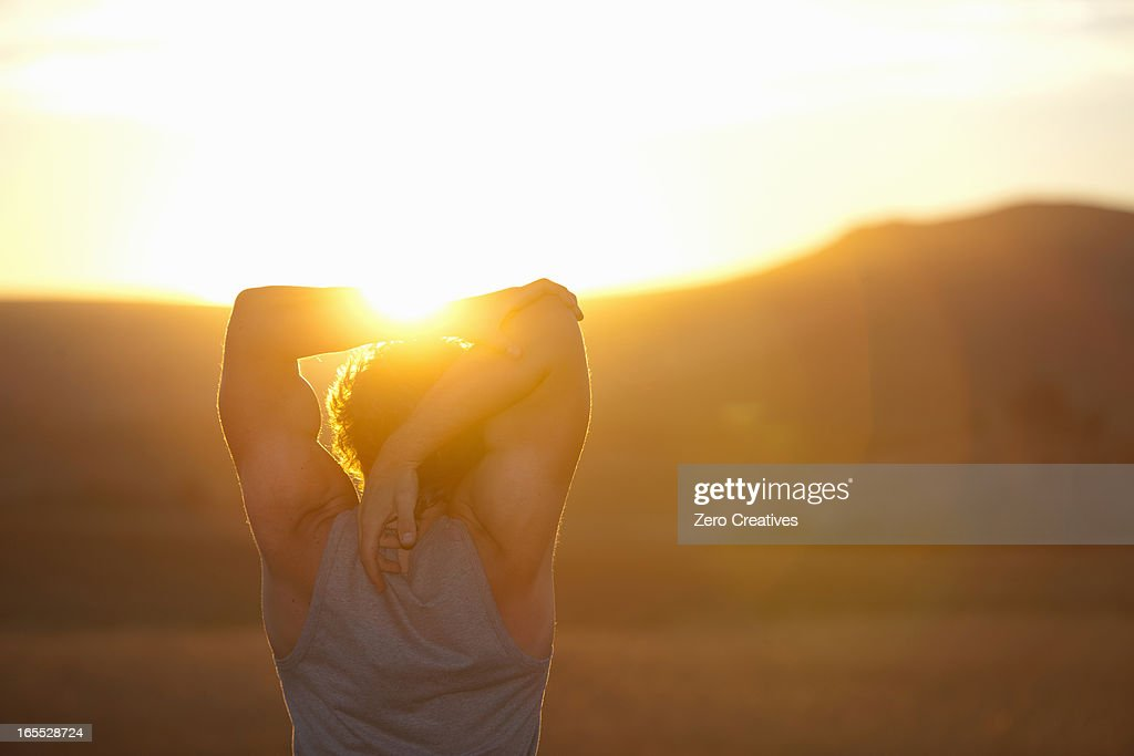 Man stretching in field at sunset