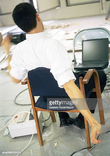 Man stretching in front of laptop computer