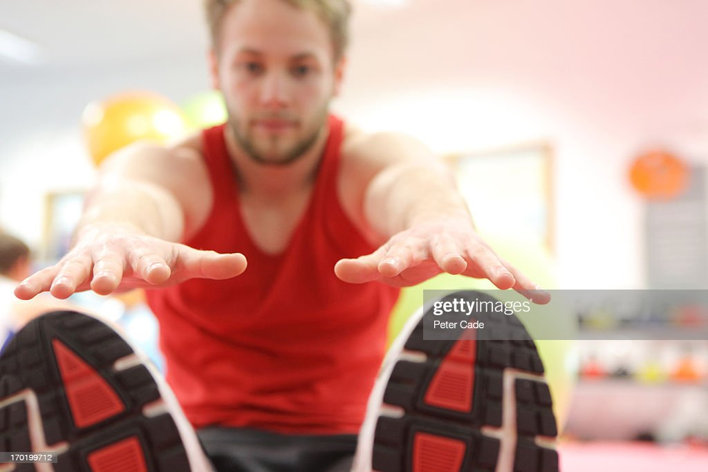 Man stretching in gym : Stock Photo