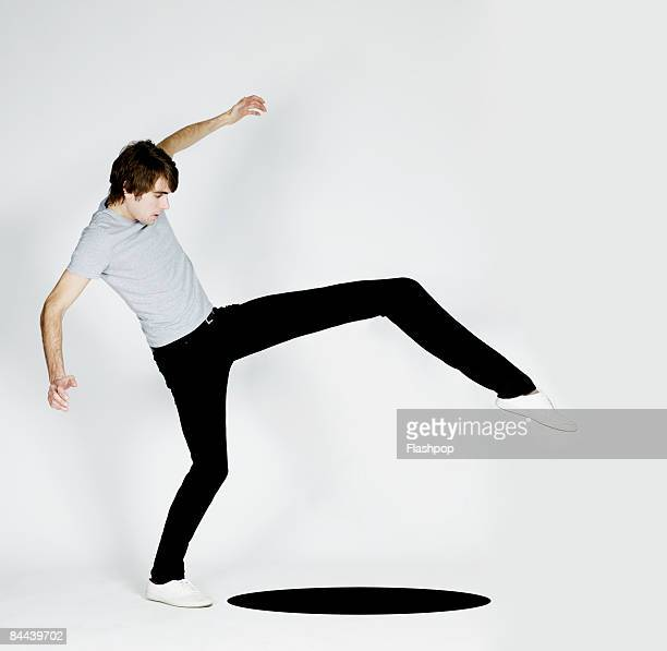 Man stretching leg to step over black hole