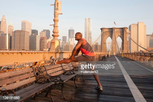 Man stretching on brooklyn bridge : Stock Photo